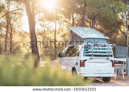 Campervan caravan vehicle for van life holiday on mobile home camper mobile motor home. Golden sunshine sneaking through sparse trees of camping. Roof of campervan is covered in colourful sunshine #1810613101