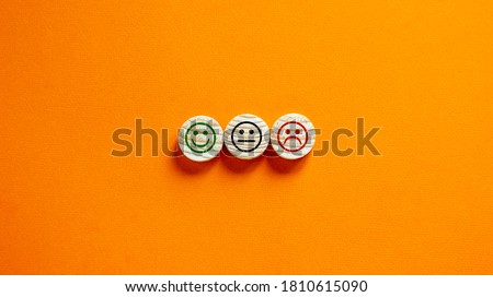 Various emoticons made of wooden circles drawn lines of a mouth. Over orange background in a conceptual image of quality and feedback. Royalty-Free Stock Photo #1810615090