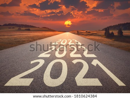 2021 2022 and 2023 new year written on highway as future and success concept against the happy looking sunset. Royalty-Free Stock Photo #1810624384