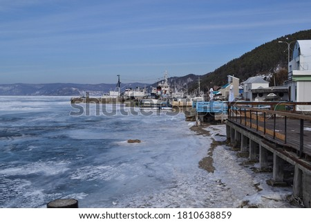 ships, port, mountains, iridescent crystals white blue ice  with cracks shine in the light the sun, the shore of lake Baikal in a snowy winter