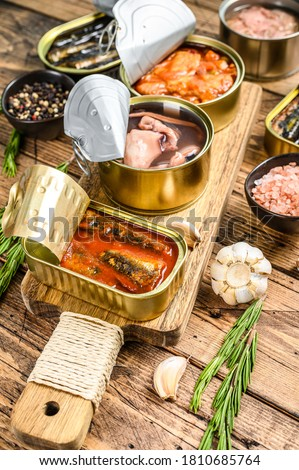Opened cans conserve with saury, salmon, sprats, sardines, squid and tuna. Wooden background. Top view Royalty-Free Stock Photo #1810685764