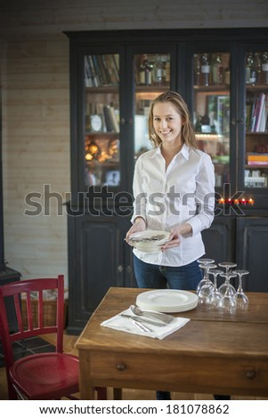 beautiful young woman getting ready to set the table at home to welcoming friends #181078862