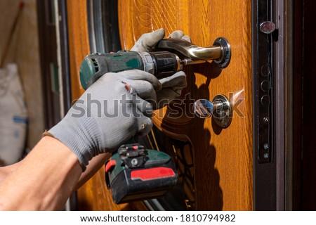 The master worker installs a door lock in the front door, metal doors with a polymer coating. #1810794982