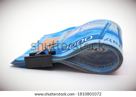 A rolled up bundle of Russian bills of 2000 rubles. Money tied with an office clip and lie on a white background with vignetting. Child support allowance and unemployment benefit in Russia. Macro