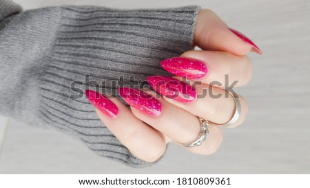 Woman hand with long nails manicure and pink fuchsia bottle with nail polish Royalty-Free Stock Photo #1810809361