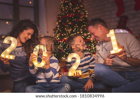 Parents celebrating New Years Eve at home with kids, sitting by the Christmas tree, holding illuminative numbers 2021 representing the upcoming New Year #1810834996