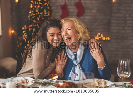 Family having Christmas dinner at home, gathered around the table, enjoying their time together; daughter hugging her mother and smiling #1810835005