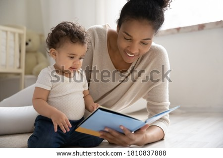 Caring young african american woman lying on warm floor with adorable little baby son or daughter, watching colorful pictures in paper book or reading fairy tale story in children room, hobby pastime.