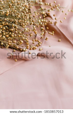 trendy Minimalistic autumn still life. Linen lies on textile fabric. Fall mood. Trend background pastel beige colors. dry flax boxes