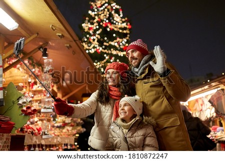family, winter holidays and technology concept - happy mother, father and little daughter taking picture by smartphone on selfie stick at christmas market on town hall square in tallinn, estonia