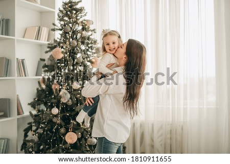 Beautiful mother and daughter have fun, hug and kiss at home near the Christmas tree in a white interior. Family happiness, holiday, joy, vacation, games with a woman. New Year's preparations. #1810911655