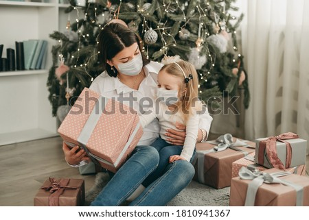 Beautiful mother and daughter in medical masks have fun at home near the Christmas tree in a white interior. Family happiness, holiday, joy, vacation, games with a woman. New Year's preparations. Cele #1810941367