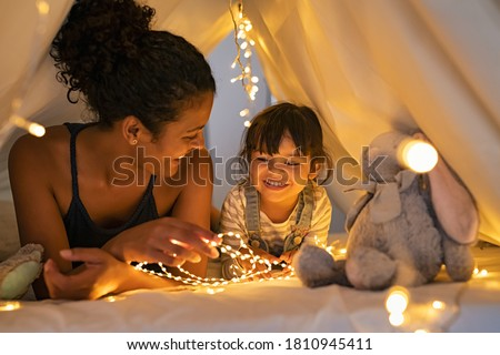 Playful mother and her daughter playing in children room in lighted tent. African mom and lovely cute girl having fun in kid hut at night at home. Mother and little daughter playing with strip lights. #1810945411