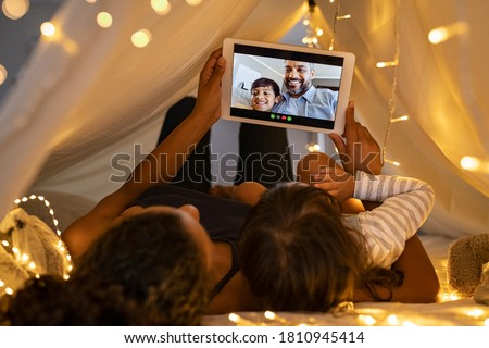 Mother and daughter using digital tablet while lying in kid tent doing a video call with father and son. Indian family in online conversation with each other during quarantine and social distancing. #1810945414