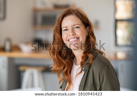 Portrait of smiling mature woman looking at camera with big grin. Successful middle aged woman at home smiling. Beautiful mid adult lady with long red hair enjoying whitening teeth treatment. Royalty-Free Stock Photo #1810945423