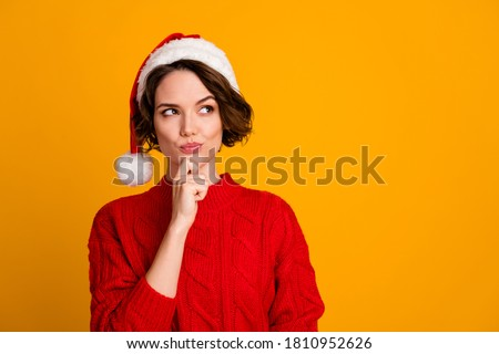 Photo of funny pretty lady celebrate winter holidays dreamy look empty space think family party hand on chin x-mas concept wear santa cap red knitted sweater isolated yellow color background Royalty-Free Stock Photo #1810952626