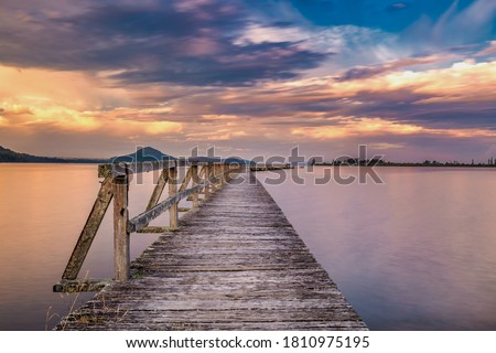Old wooden wharf shot with long exposure during sunset. Location is Tokaanu Wharf located in Taupo region of North Island, New Zealand. #1810975195