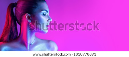Colorful portrait of a beautiful young woman over purple background. High Fashion model woman in colorful bright neon lights posing in studio, night club. Portrait of beautiful girl in UV. Art design  Royalty-Free Stock Photo #1810978891