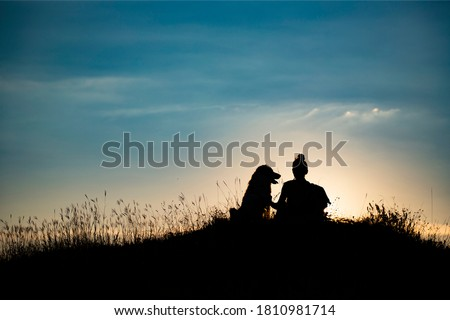 Silhouette of young woman with her dog in the sunset outdoor. Royalty-Free Stock Photo #1810981714