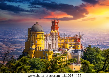 Famous historic Pena palace part of cultural site of Sintra against sunset sky in Portugal. Panoramic View Of Pena Palace, Sintra, Portugal. Pena National Palace at sunset, Sintra, Portugal.  Royalty-Free Stock Photo #1810984492