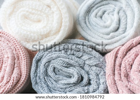 warm winter clothes. rolled grey and pink sweaters in a pile. cold weather clothing. wool texture. variety of soft alpaca fabric for kids cothes.