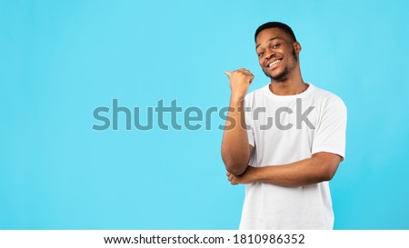 Black Guy Pointing Thumb Aside At Blank Space For Text Standing On Blue Studio Background. Look There Concept. Panorama Royalty-Free Stock Photo #1810986352