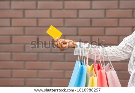 Discount for shop and payment for purchase. African american woman with multicolored packages gives credit card, free space Royalty-Free Stock Photo #1810988257