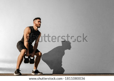 Strong young muscular focused fit man with big muscles holding heavy kettlebells Royalty-Free Stock Photo #1811080036