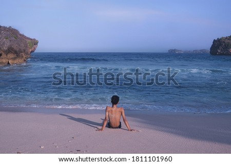 calm beach atmosphere with a man staring at the sea #1811101960