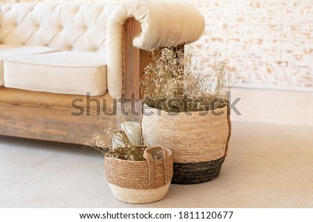 Wicker baskets with dried flowersnear the sofa on floor. Living room hygge, autumn cozy home decor. Scandinavian interior. Comfortable bedroom in bohemian interior style. Rustic. dry plants in vase Royalty-Free Stock Photo #1811120677