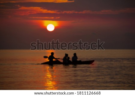 Blurred picture, family kayak excursion in the sunset, admiring the beauty of nature.