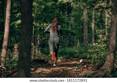 Exercising outdoors is healthy for active lifestyle runners. Autumn trail run woman running in nature from behind in dark forest. Outdoor jog. Royalty-Free Stock Photo #1811172892