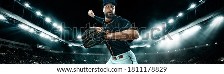 Wide photo. Porfessional baseball player with ball on grand arena. Ballplayer on stadium in action. Royalty-Free Stock Photo #1811178829