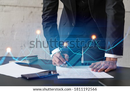 Businessman in suit signs contract. Double exposure with financial chart hologram. Man signing mortgage agreement. Real estate market analysis and investment concept. Royalty-Free Stock Photo #1811192566