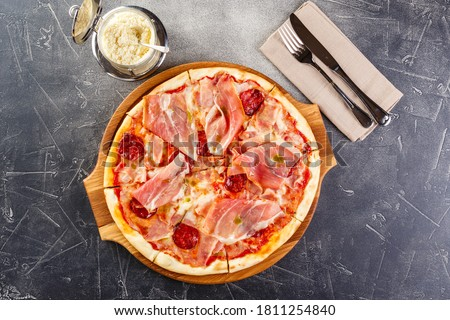 Pizza with salami and prosciutto on wooden board on dark background Royalty-Free Stock Photo #1811254840