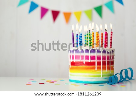 Rainbow birthday cake with colorful candles and drip icing Royalty-Free Stock Photo #1811261209