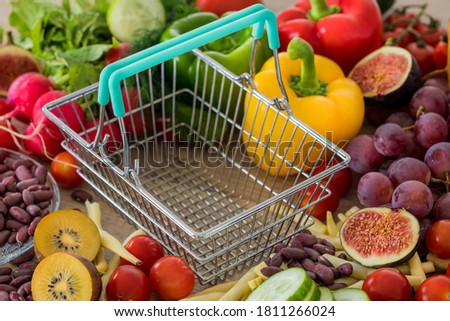 Empty shopping Cart. Lots of food, vegetables and fruits around. The concept of rising prices, inflation and more expensive food Royalty-Free Stock Photo #1811266024