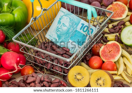 Shopping basket with Brazilian money, around food products, vegetables and fruits.  The concept of inflation, rising prices and more expensive food Royalty-Free Stock Photo #1811266111