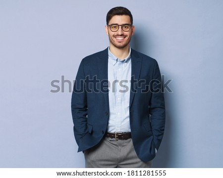 Young business man wearing formal clothes and eyeglasses, standing isolated against blue background in relaxed pose, smiling friendly Royalty-Free Stock Photo #1811281555