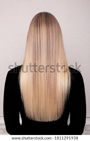 Female back with long blonde healthy hair in hairdressing salon Royalty-Free Stock Photo #1811291938