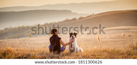 woman with dog relaxing in autumn landscape