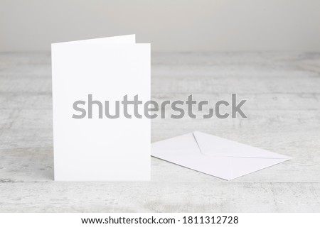 One white greeting card mockup with envelope, standing upright on a white wooden desk. Blank, closed card template.  Royalty-Free Stock Photo #1811312728