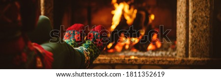Feet in woollen socks by the fireplace. Woman relaxes by warm fire and warming up her feet in woollen socks. Staying at home during quarantine. Winter and Christmas holidays concept. Banner format. #1811352619