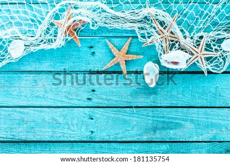 Delicate nautical border with fishing net, sea shells and starfish on a background of colourful turquoise blue painted wooden boards with copyspace for your text Royalty-Free Stock Photo #181135754
