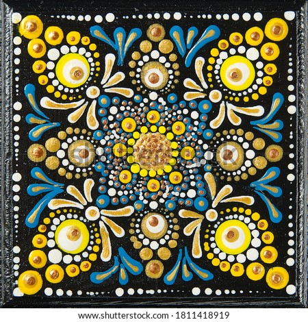 Mandala dot art painting on wood tiles. Beautiful mandala hand painted by colorful dots on black wood. National patterns with acrylic paints, handwork, dot painting. Abstract dotted background. #1811418919