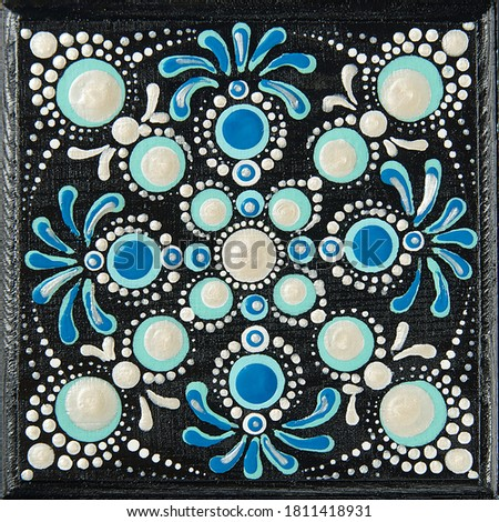 Mandala dot art painting on wood tiles. Beautiful mandala hand painted by colorful dots on black wood. National patterns with acrylic paints, handwork, dot painting. Abstract dotted background. #1811418931
