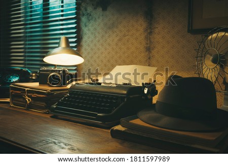 Office desk with vintage typewriter and fedora hat, 1950s film noir style Royalty-Free Stock Photo #1811597989