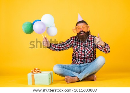 holiday celebration. bearded mature man celebrate birthday party. cheerful man in bday hat hold holiday balloons. gifts and presents concept. have a happy holiday. party time. happy birthday to you.