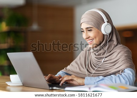 Cheerful muslim woman studying online on laptop, typing on keyboard, cafe interior, free space Royalty-Free Stock Photo #1811621677