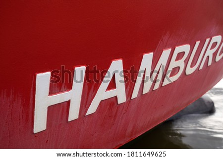 Detail of an old fishing boat. Hamburg letters. Bright rusty details. Design of an old ship. Detail of a traditional fishing boat.